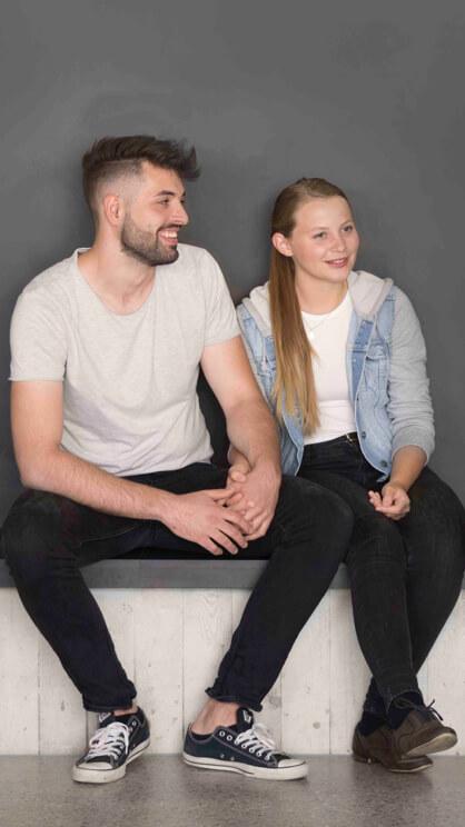 Eine junge Frau und ein junger Mann sitzen auf einer Bank und halten sich an den Haenden
