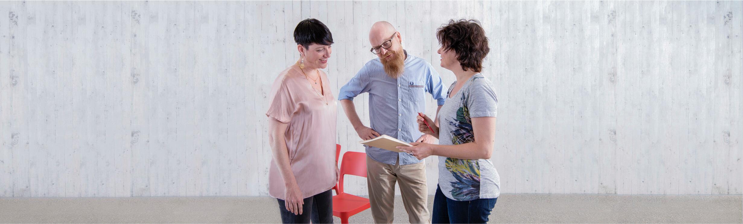 Drei Personen stehen zusammen und unterhalten sich