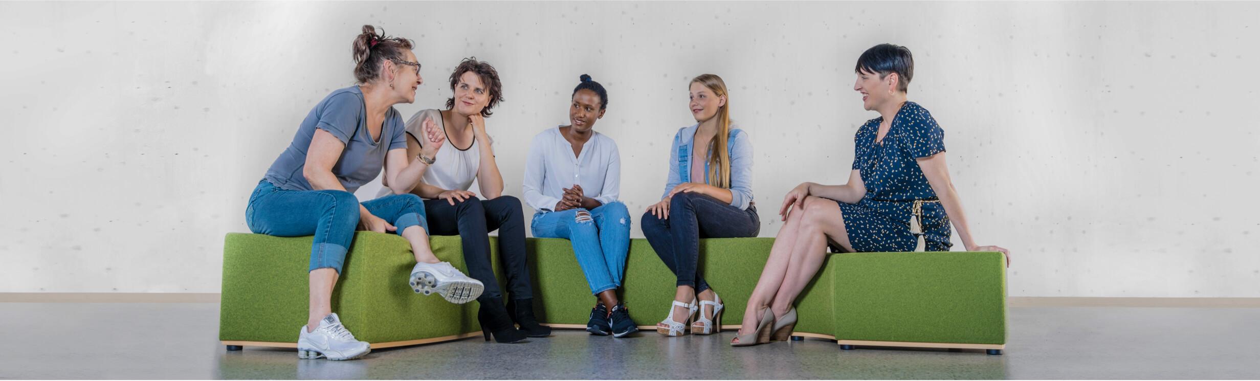 Fuenf Frauen sitzen in einer Runde und unterhalten sich